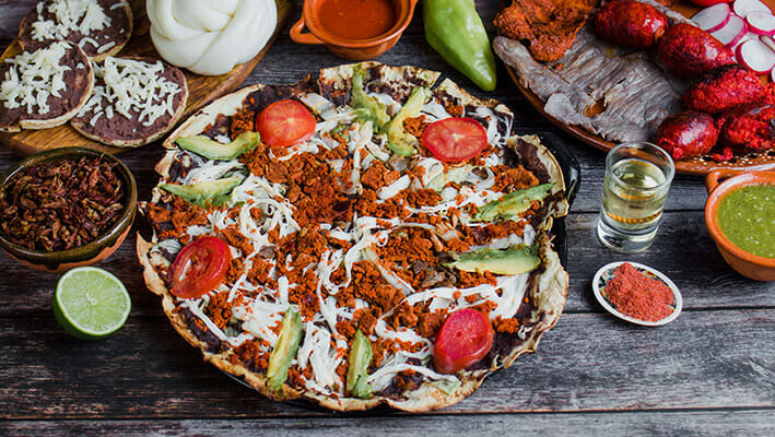 Mexican Tlayuda Pizza on tortilla bread with ground beef