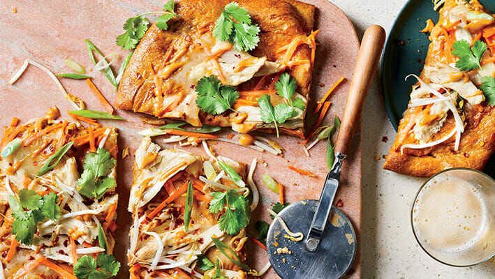 Thai Pizza with peanuts, parsley and raw vegetables