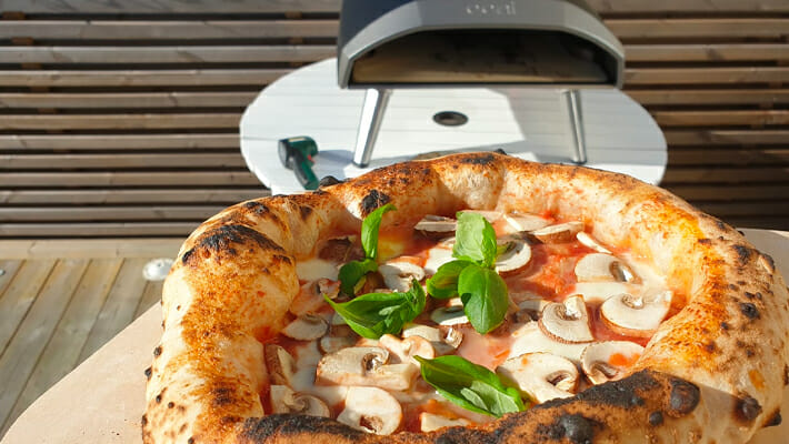 A pizza with mushrooms on and an Ooni Koda 16 in the background