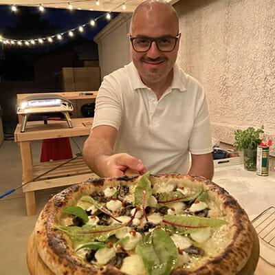Ismaele Romano holding a pizza