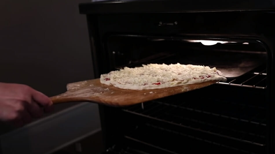 Placing NY-style pizza into conventional oven